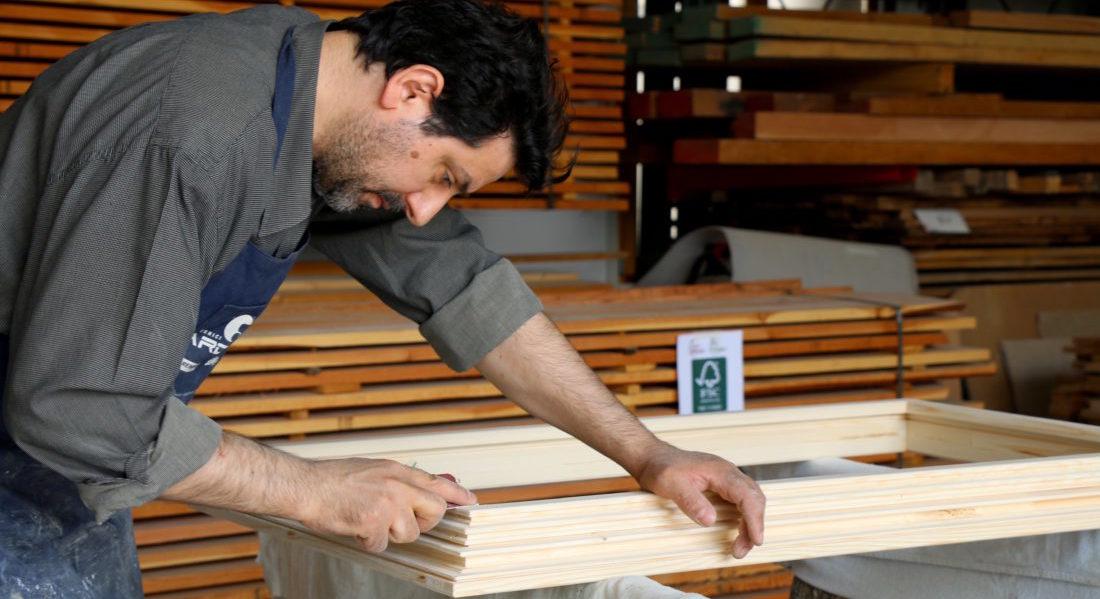 Un artigiano lavora un serramento in legno certificato